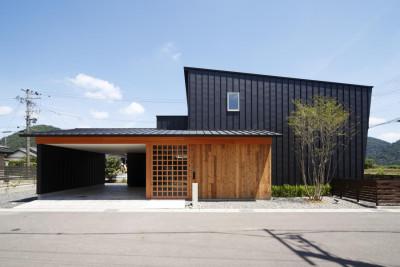 和モダンの住宅。黒いガルバリウムと木の外壁