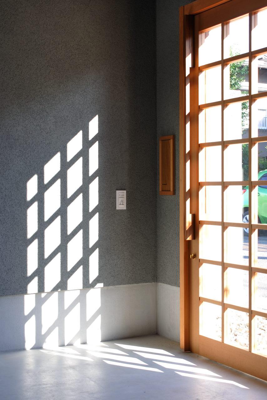 玄関格子扉からの光と影